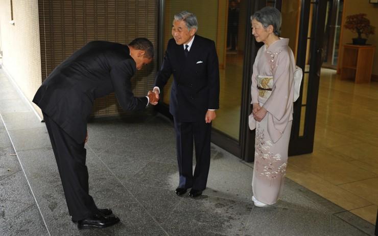 US President Barack Obama (L) bows as he