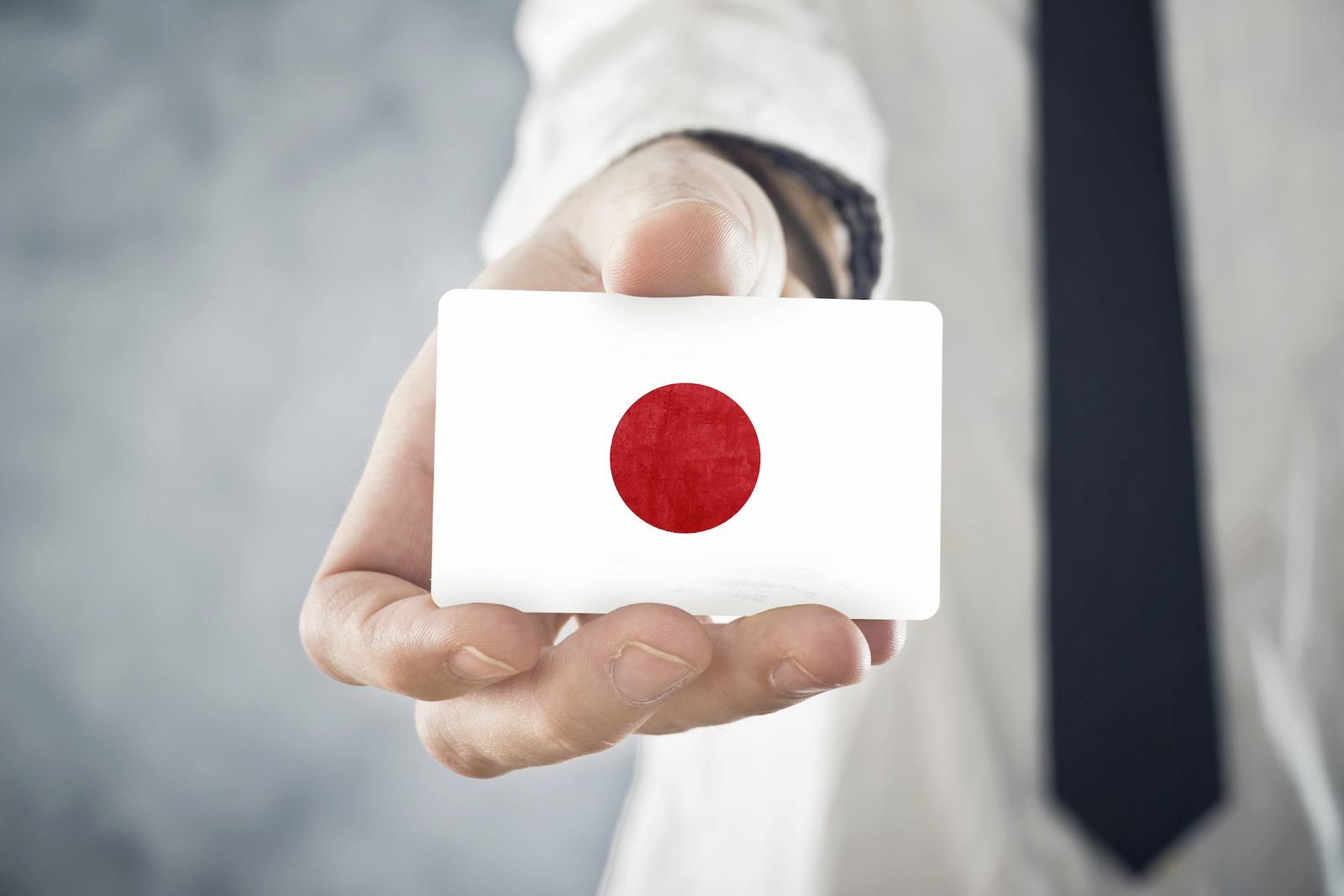 Japanese Businessman holding business card with Japan Flag - GaijinPot