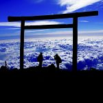 Sunrise at the top of Mount Fuji with a silhouette of people