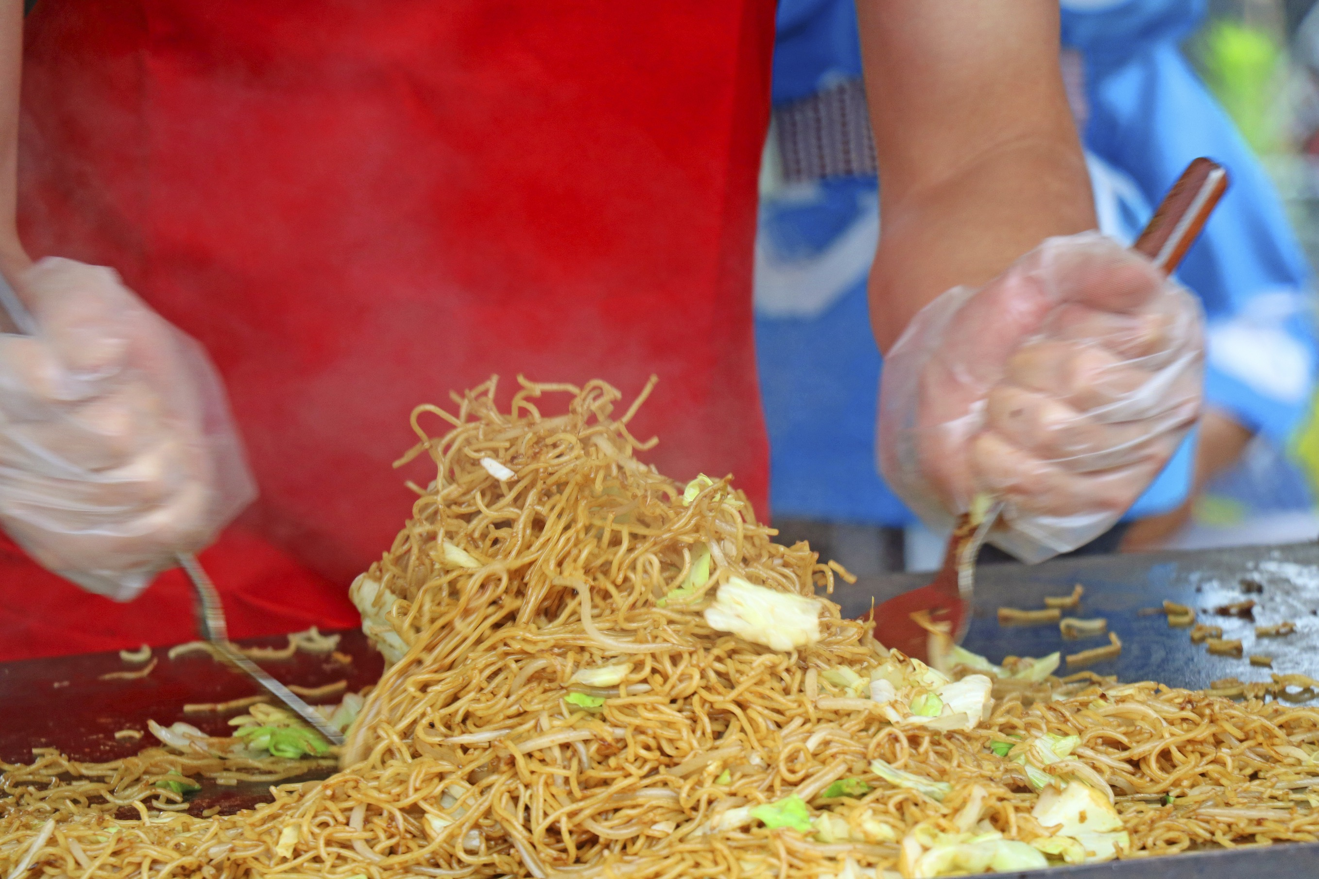 Person making yakisoba at a Japanese festival