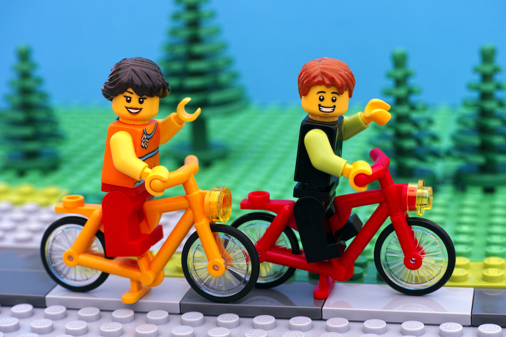 Lego boy and girl riding bikes in park