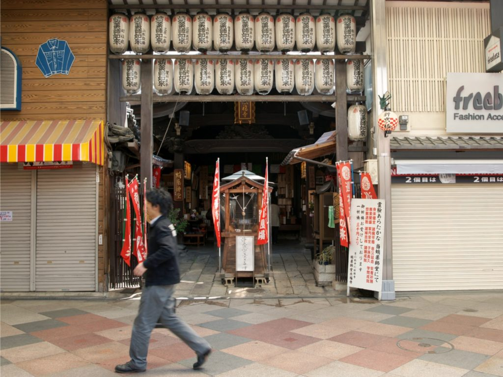 A Young Salary Man Walking in front of a Temple frontage Displaying Sponsor Lanterns inside a Shopping Arcade