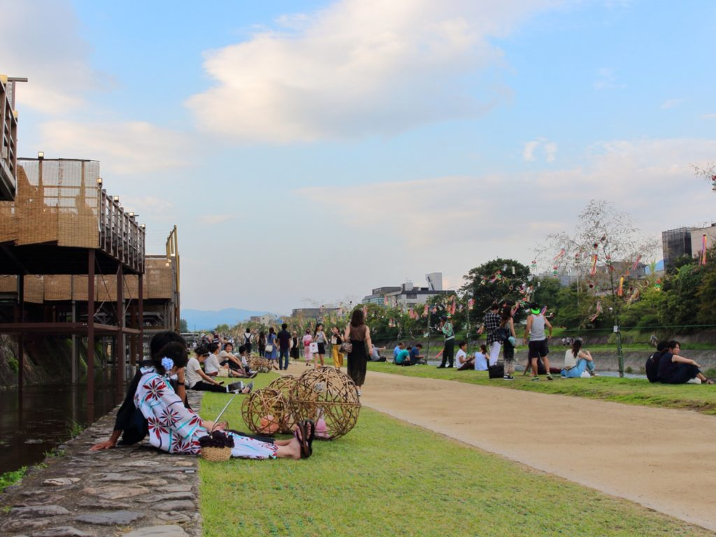 People relaxing in Kamo river. Its riverbanks are popular walking spots for residents and tourists.