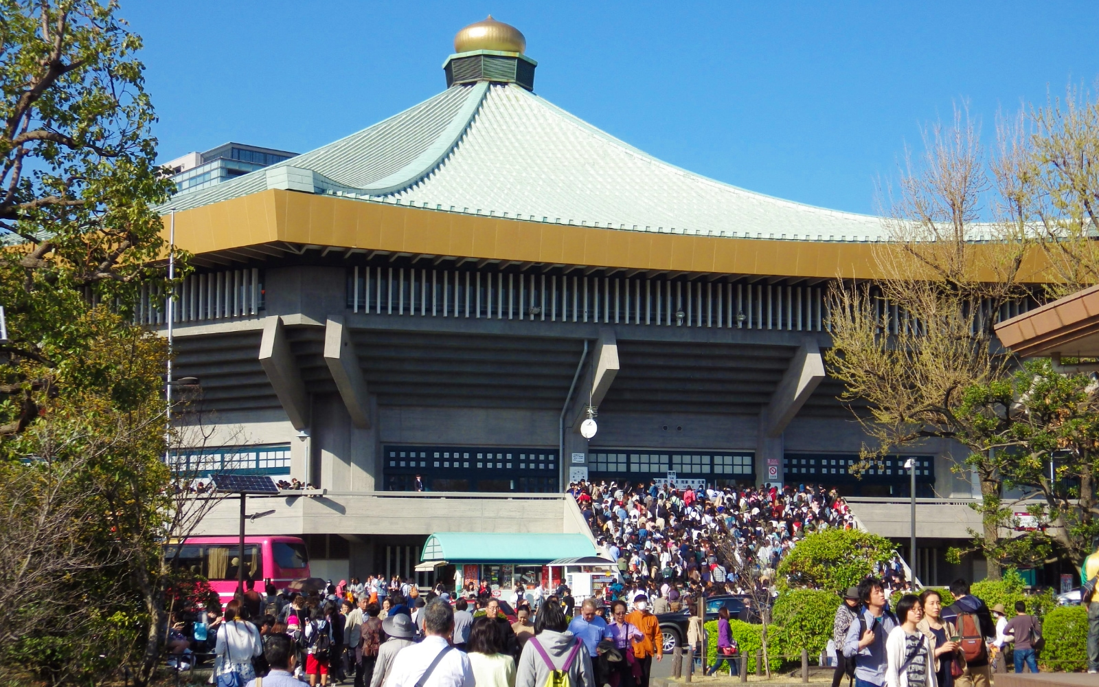 People lining up outside the Budokan arena for an event.
