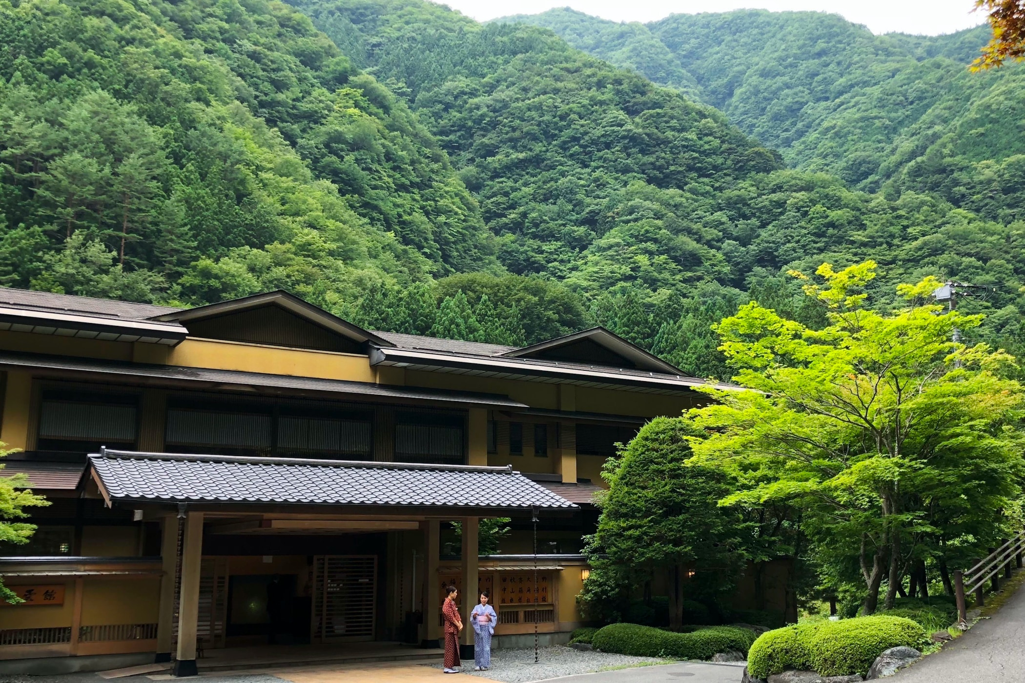 The Nishiyama Onsen Keiunkan, the world's oldest hotel, with mountains behind it and staff in kimono ready to greet guests out front.