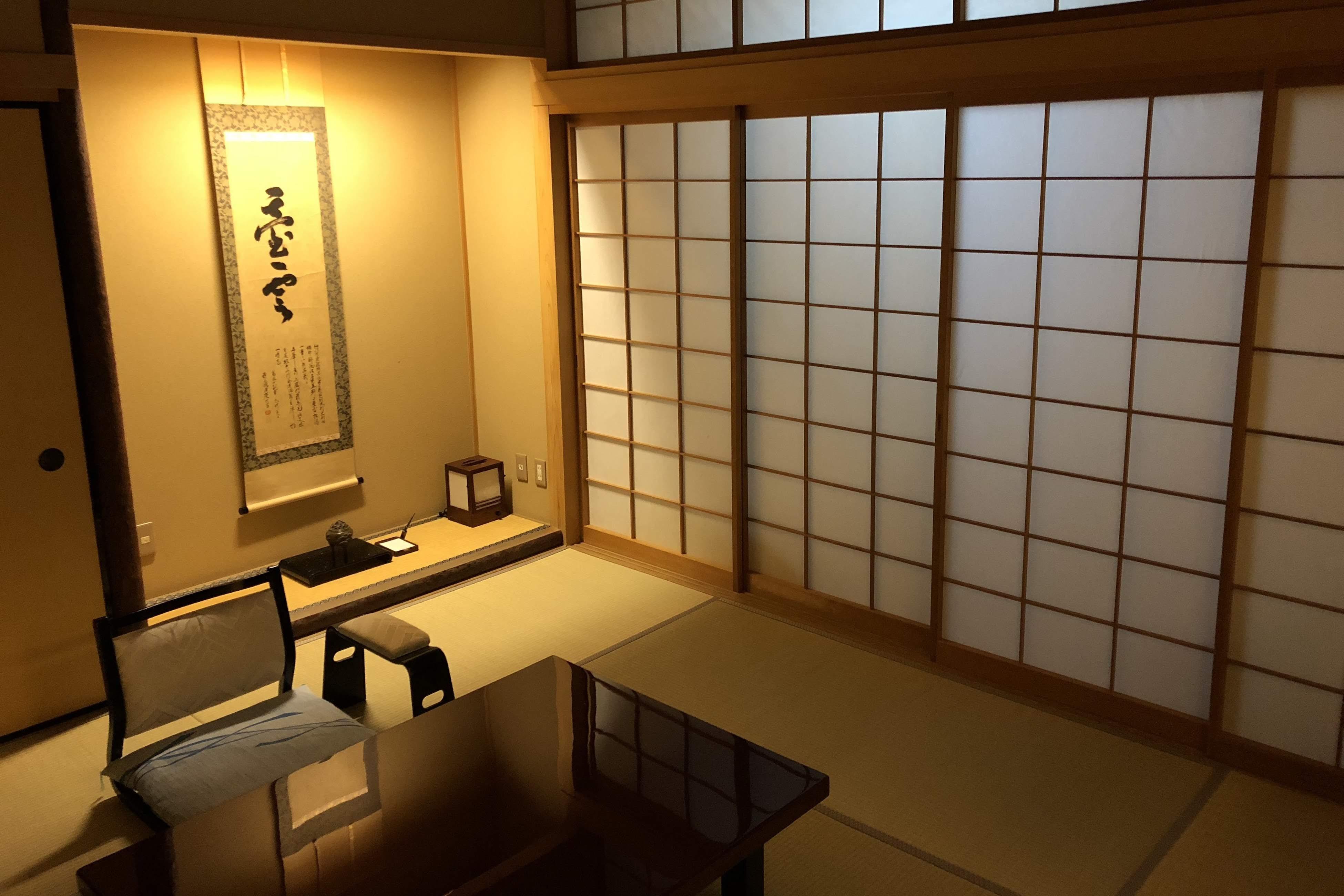 In the room at night with the kakejiku (hanging scroll) corner and shoji doors illuminated.