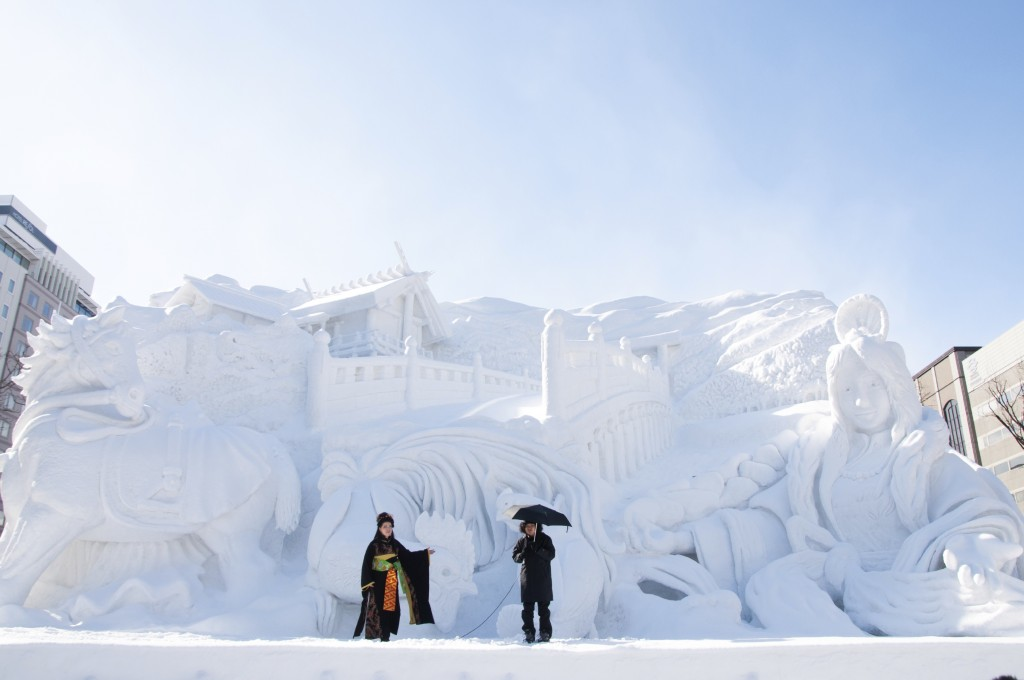 Performers stand in front of a giant snow sculpture at the Sapporo snow festival
