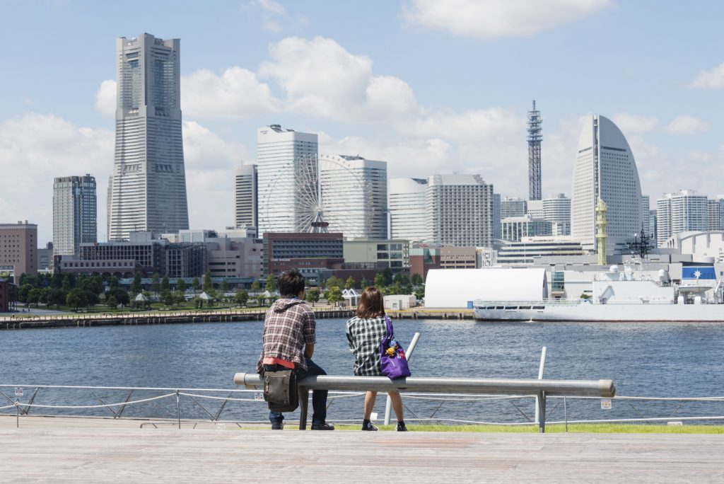 """Yokohama, Japan - August 27, 2013: A young couple are seated on the bench at the Osanbashi Pier in Yokohama, Japan. They are looking at the skyline of the city."""