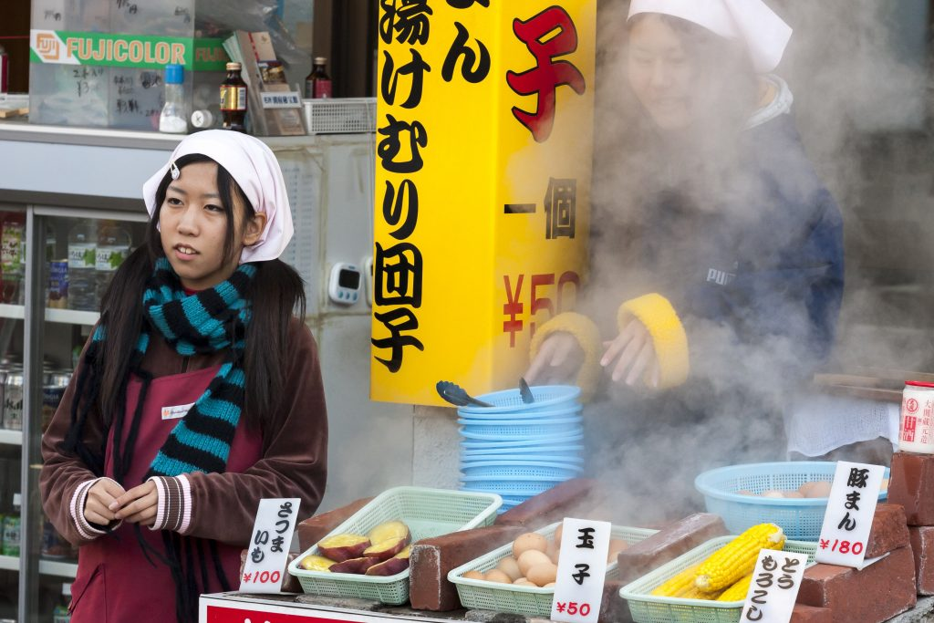 Beppu, Japan - December 29, 2009: Two young girls are cooking food on outdoors market. Boled eggs, corn and potatoes is popular fast food in Beppu, Japan