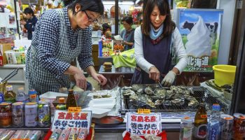 Miyajima, Japan - November 15 2013: Unidentified vendors sell grilled oyster with soy sauce to tourist which is very popular amongst the people at Omotesando Shopping Street